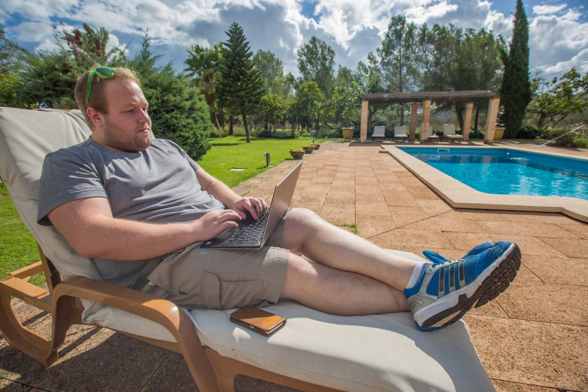 Jojo beim Arbeiten mit Laptop am Pool