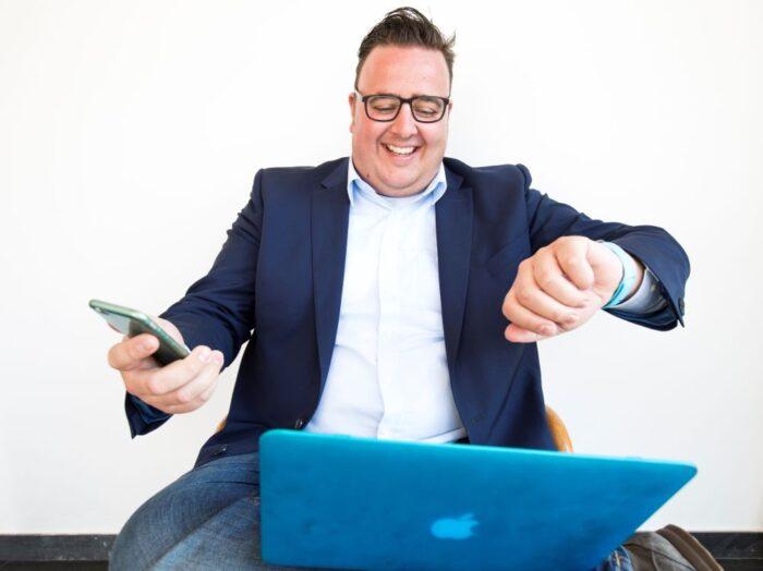 Michael mit Laptop, Smartphone und Smartwatch