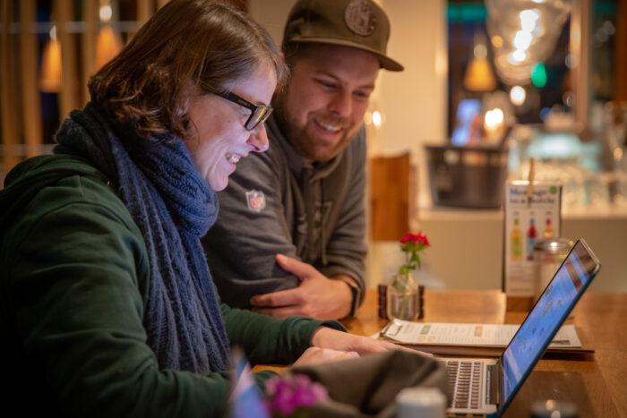 Zwei Personen an einem Rechner sitzend. Lächelnd.