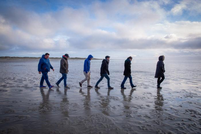 6 Menschen, hintereinander laufend am Strand/im Watt