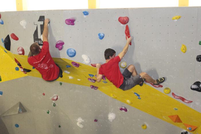 Zwei Jungs, die an einer Kletterwand klettern