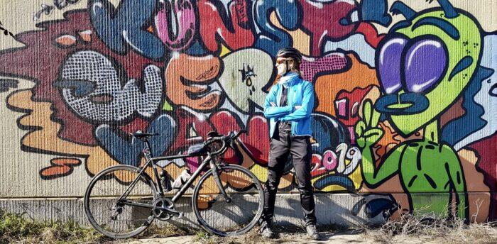 Anna Scheffold, Beraterin bei Tourismuszukunft mit Rennrad vor bunter Graffiti-Wand